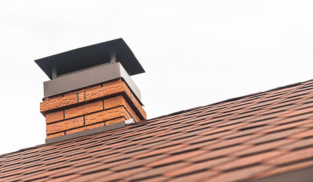 Chimney pipe in red bricks on roof in red shingles